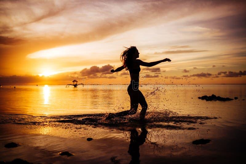 Caminhada da mulher na praia no por do sol imagens de stock