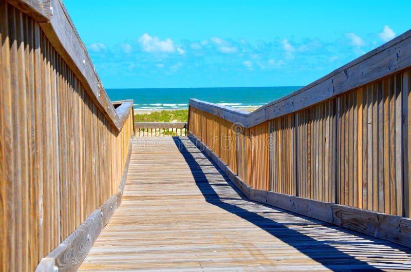 Caminhada da ponte de madeira à praia do oceano fotos de stock royalty free