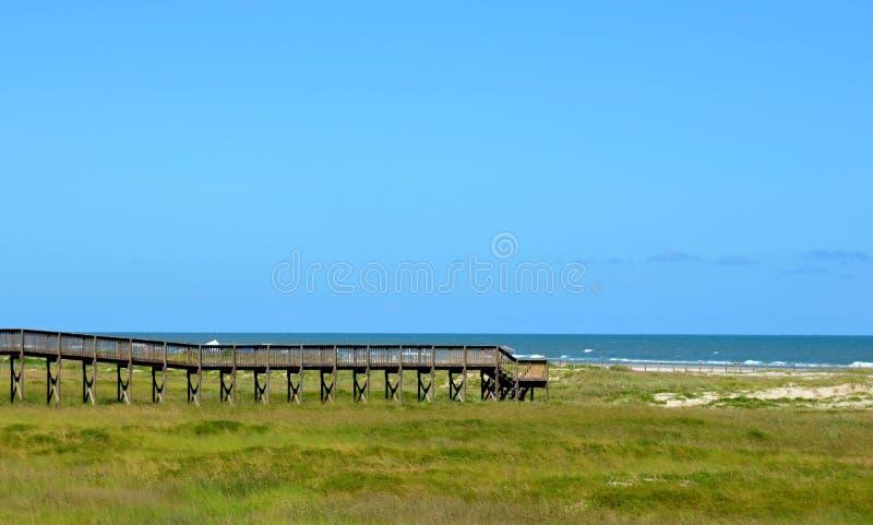 Caminhada da ponte de madeira à praia do oceano fotografia de stock royalty free