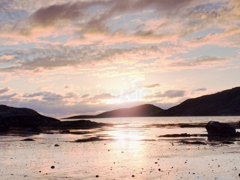 Caminhada dentro do por do sol na praia Espelhar do horizonte sunsetting na água do mar entre rochas foto de stock