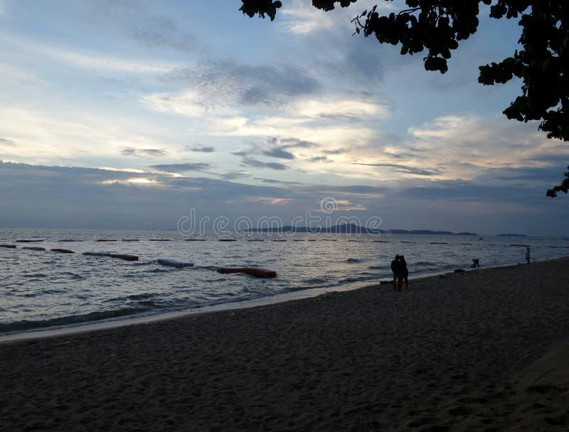 Caminhada do amante na praia quieta longa romântica sob o céu bonito imagens de stock royalty free