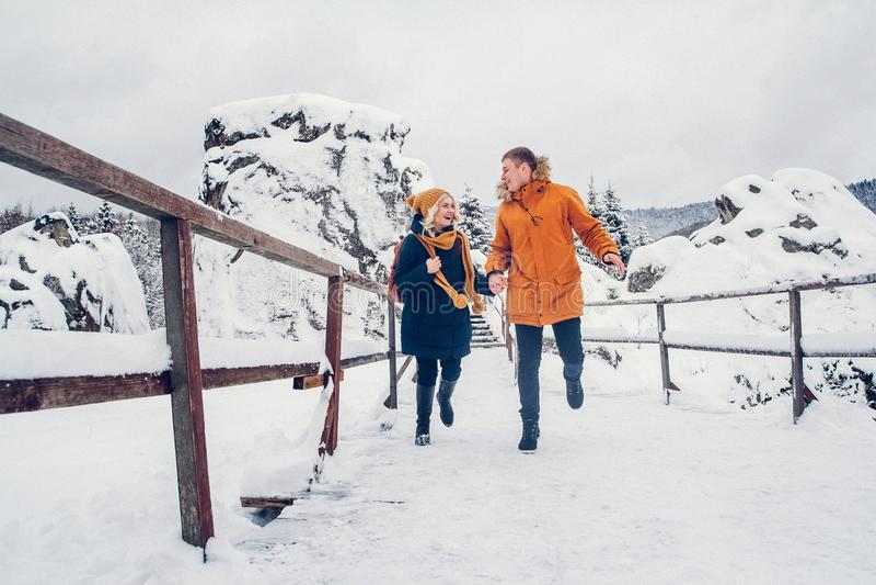 Caminhada do indivíduo e da menina e para ter o divertimento na floresta no inverno imagens de stock