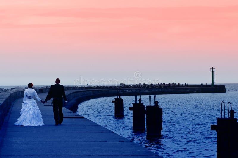 Caminhada do por do sol do mar dos Newlyweds foto de stock