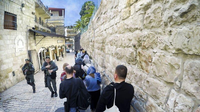Caminhada do turista na rua de pedra estreita da aleia com a segurança do exército da polícia que fixa povos dos ataques do thero foto de stock