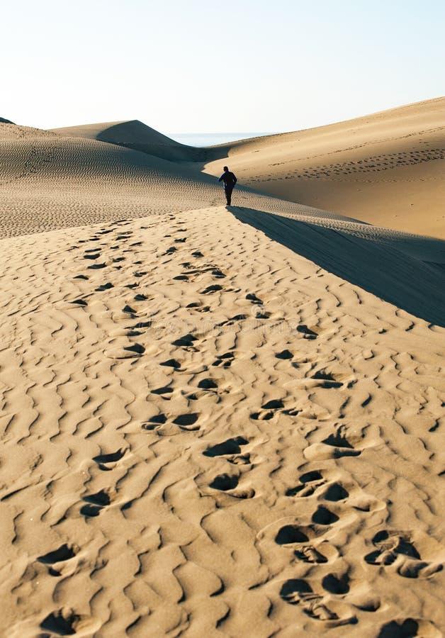 Caminhada dos homens em dunas de Maspalomas imagens de stock