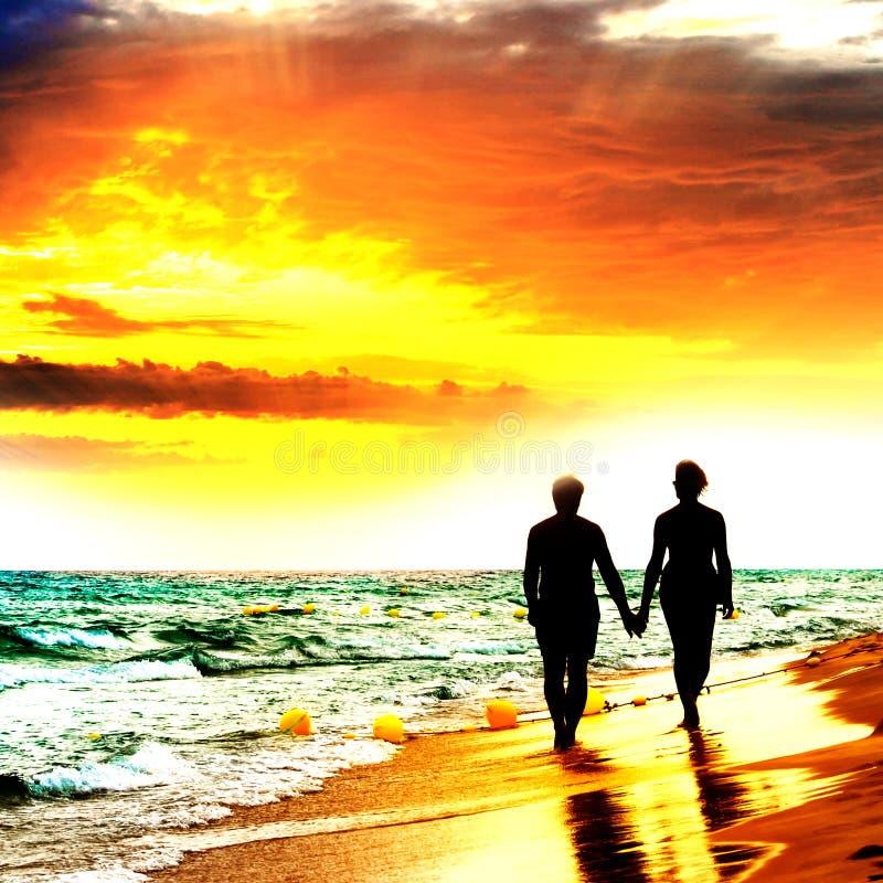 Caminhada dos pares na praia fotografia de stock