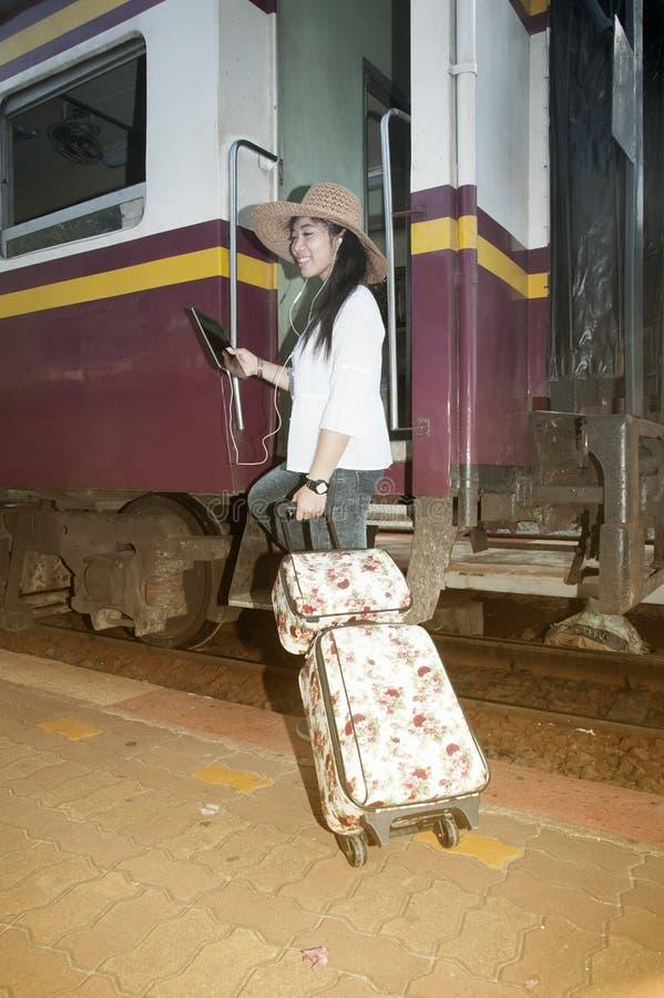 Caminhada e posição asiáticas bonitas do viajante das mulheres no trem fotografia de stock royalty free