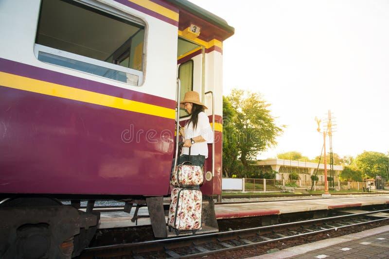Caminhada e posição asiáticas bonitas do viajante das mulheres no trem fotografia de stock