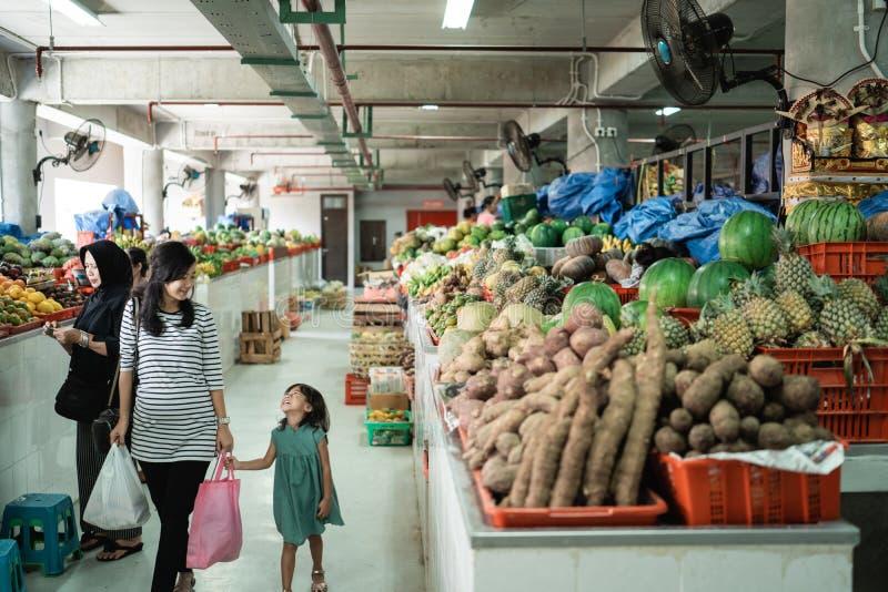 Caminhada grávida da jovem mulher com seu saco de plástico levando da filha fotografia de stock