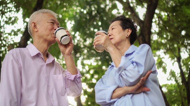 Caminhada idosa asiática feliz da manhã dos pares na cidade verde quando drin foto de stock royalty free