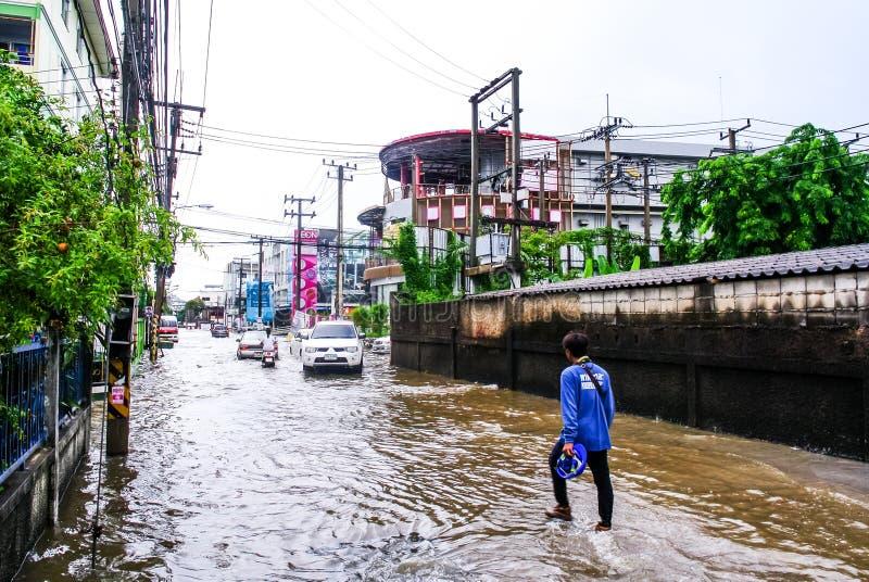 Caminhada não identificada do homem através da inundação após a chuva na cidade de Sriracha fotografia de stock