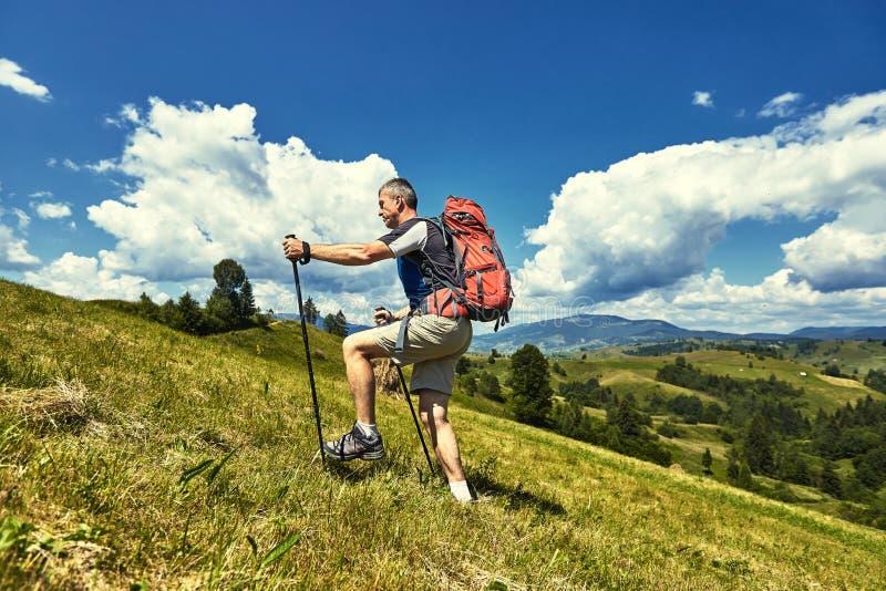 Caminhada nas montanhas no verão com uma trouxa imagem de stock