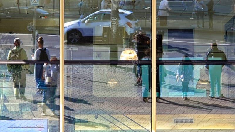 Caminhada nos pedestres coloridos do dia de verão do fundo urbano dos carros da rua, caminhante dos povos da reflexão das janelas foto de stock royalty free