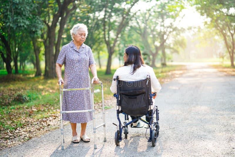A caminhada paciente asiática da mulher superior ou idosa da senhora idosa com caminhante cumprimenta o amigo da Idade Média na c foto de stock