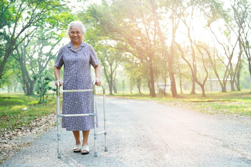 Caminhada paciente asiática da mulher superior ou idosa da senhora idosa com o caminhante no parque foto de stock