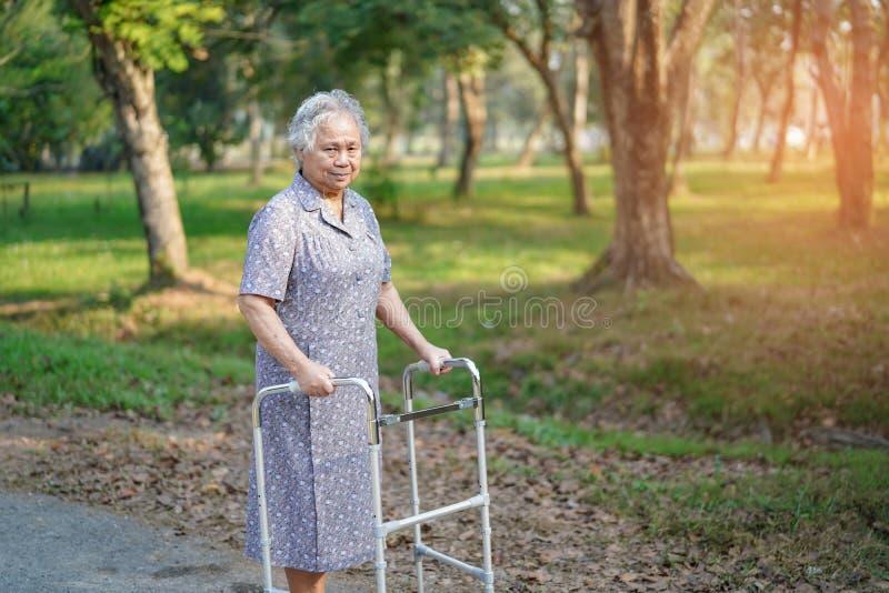 Caminhada paciente asi?tica da mulher superior ou idosa da senhora idosa com o caminhante no parque imagens de stock royalty free