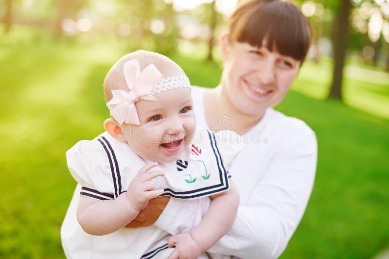 Caminhadas bonitas da mãe e do bebê da foto do verão do estilo de vida no parque imagens de stock