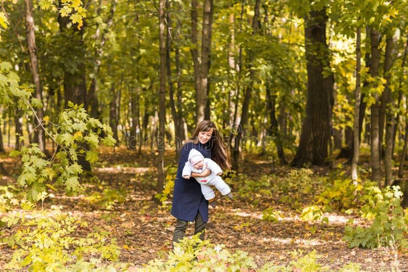 Caminhadas bonitas no parque, luz solar morna da mãe e da criança da foto do outono do estilo de vida imagem de stock
