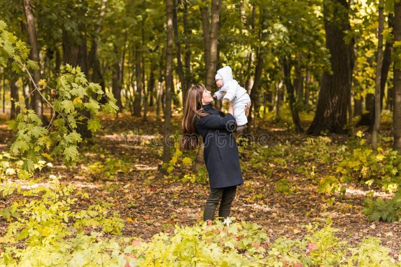 Caminhadas bonitas no parque, luz solar morna da mãe e da criança da foto do outono do estilo de vida fotos de stock