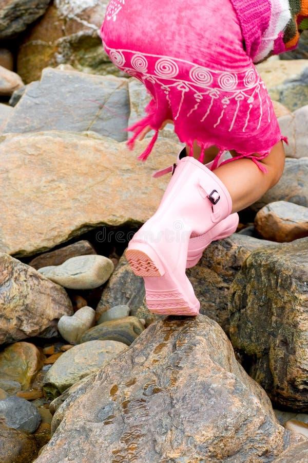 Caminhadas da menina com cuidado em rochas fotos de stock royalty free
