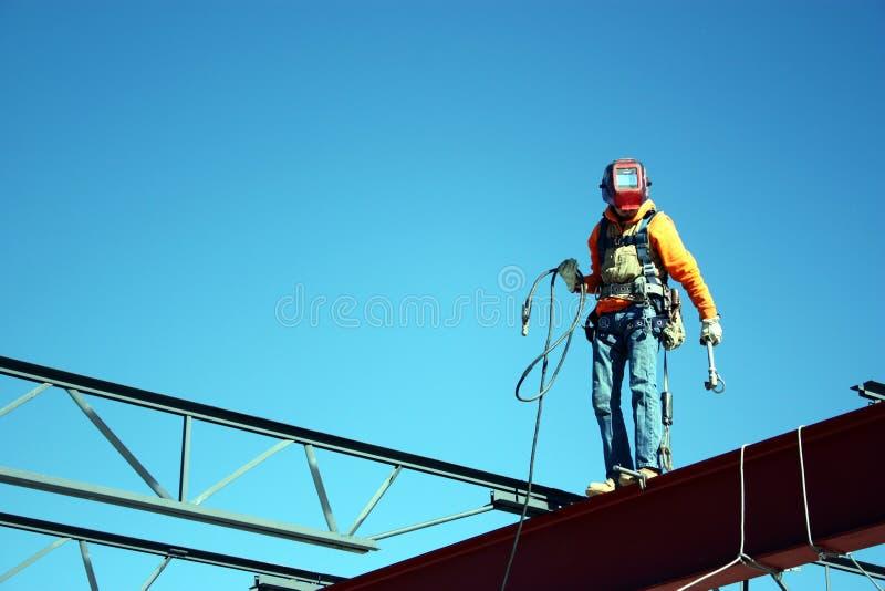 Caminhadas do trabalhador do ferro um feixe fotografia de stock