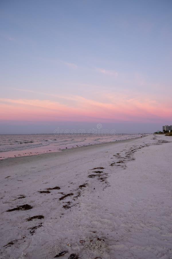 Caminhadas do turista ao longo de um Golfo do México agitado no dur da ilha de Estero fotografia de stock