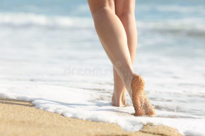 Caminhadas dos pés da menina na areia e na água do mar na praia fotos de stock royalty free