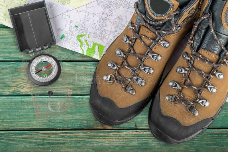 Caminhando botas, compasso e mapa no fundo de madeira fotografia de stock