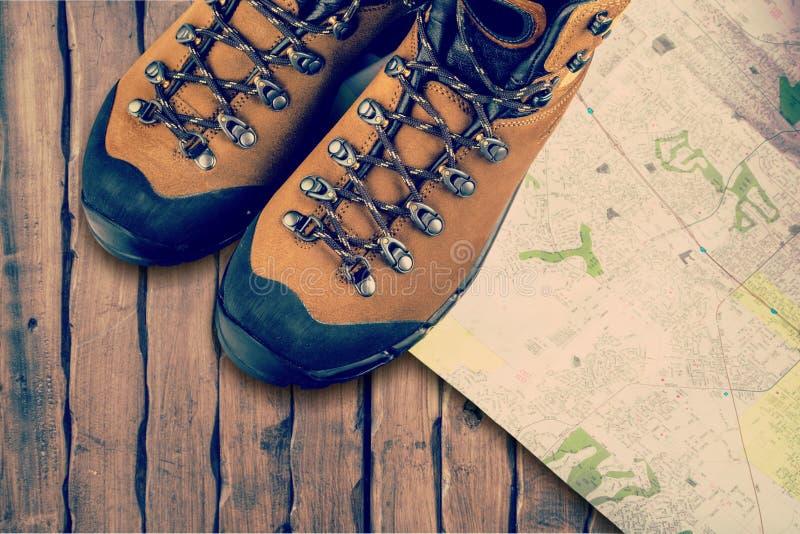 Caminhando botas e mapa no fundo de madeira fotografia de stock royalty free