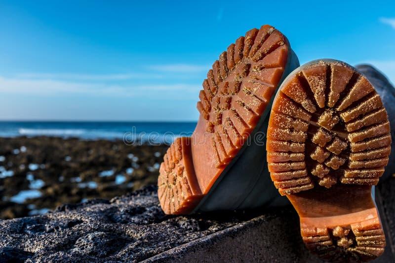 Caminhando botas em uma praia foto de stock royalty free