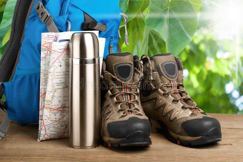 Caminhando botas, trouxa e mapa no fundo fotografia de stock royalty free
