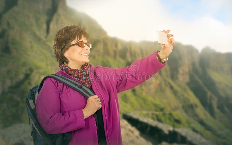 Caminhando a mulher adulta que fotografa montanhas imagens de stock royalty free