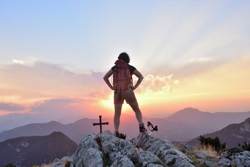 Caminhando a mulher com mãos em sua cintura que olha o por do sol imagens de stock royalty free