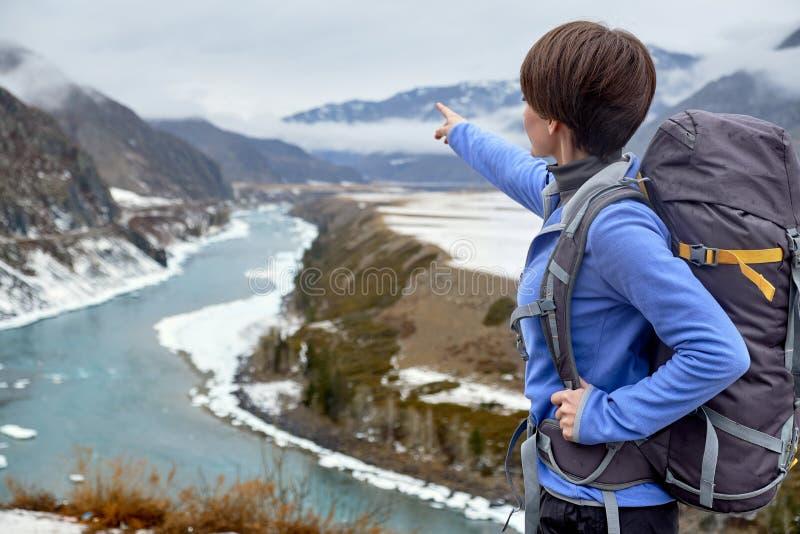 Caminhando a mulher de sorriso com uma trouxa nas montanhas A moça bonita está viajando nas montanhas imagem de stock