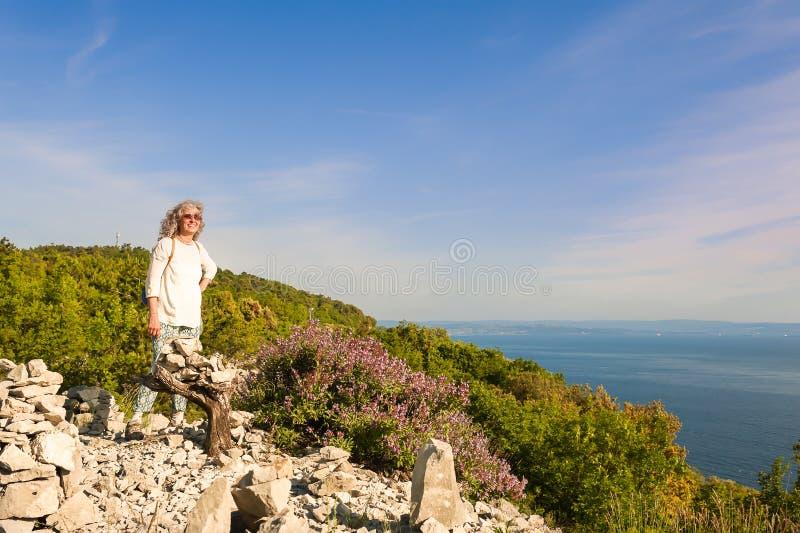 Caminhando a mulher no penhasco que aprecia a opinião ensolarado do mar fotografia de stock royalty free