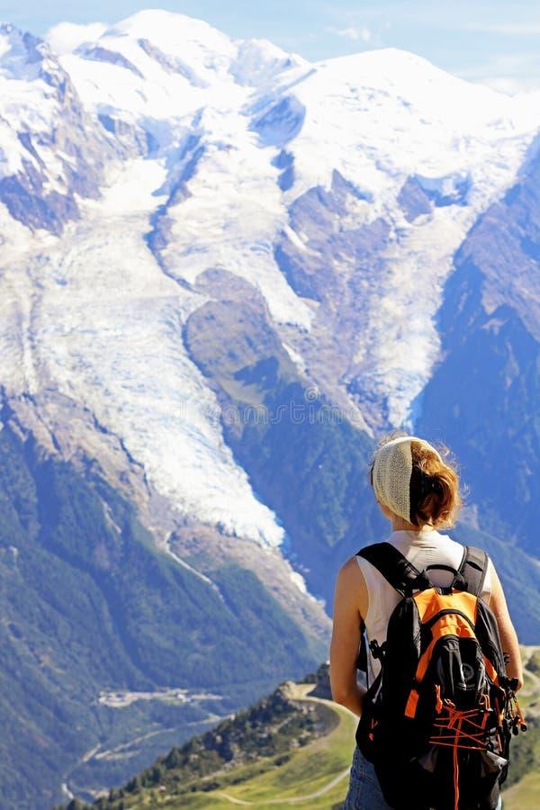 caminhando a mulher que admira a cimeira de Mont Blanc em Chamonix, france imagem de stock