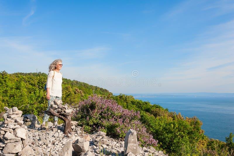 Caminhando a mulher que aprecia a opinião ensolarado do mar imagem de stock royalty free