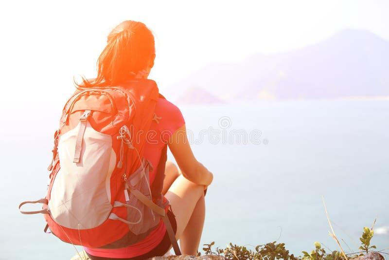 Caminhando a mulher sente a rocha do beira-mar fotografia de stock
