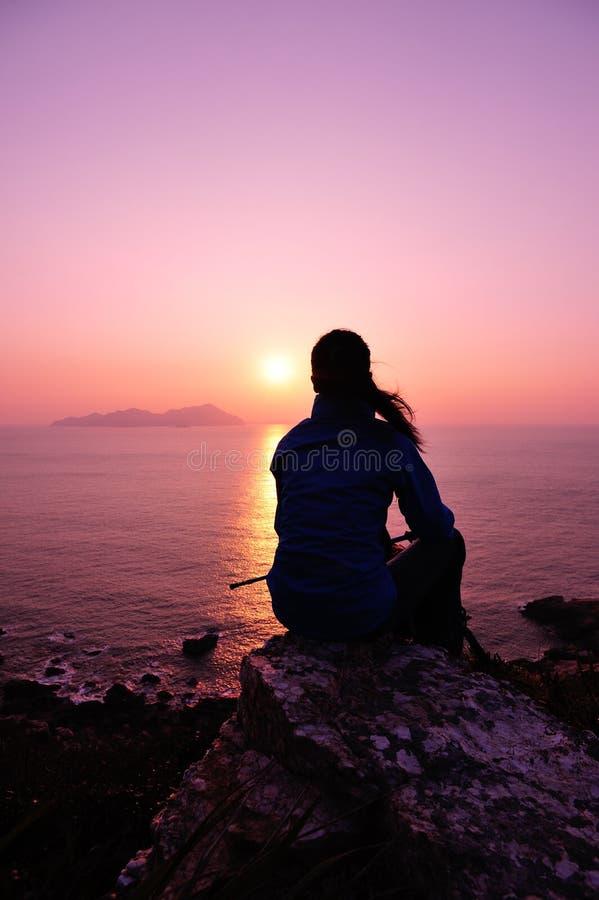Caminhando a mulher sente-se no beira-mar do nascer do sol fotos de stock