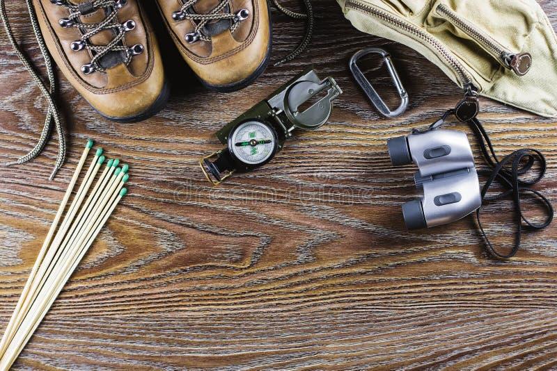 Caminhando o equipamento com botas, compasso, binóculos, fósforos, saco do curso no fundo de madeira Conceito ativo do estilo de  imagem de stock