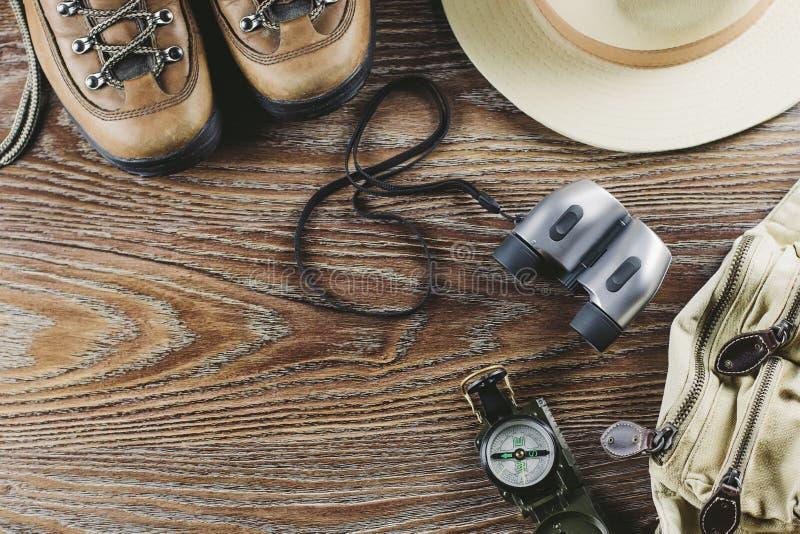 Caminhando o equipamento com botas, compasso, binóculos, fósforos, saco do curso no fundo de madeira Conceito ativo do estilo de  foto de stock