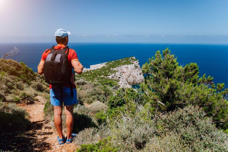 Caminhando o homem do turista na frente do seascape bonito Caminhante que trekking com a trouxa no trajeto rochoso da fuga Estilo fotos de stock royalty free
