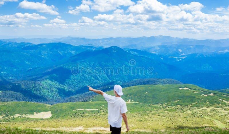 Caminhando o homem que aponta em algo com sua mão Viagem do moderno O homem mostra o sentido com sua posição da mão fotos de stock royalty free