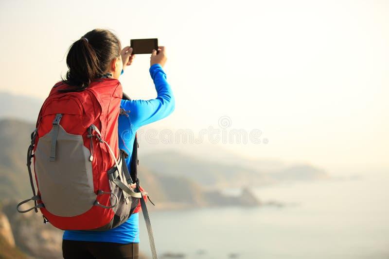 Caminhando o telefone esperto do uso da mulher que toma a foto fotos de stock royalty free