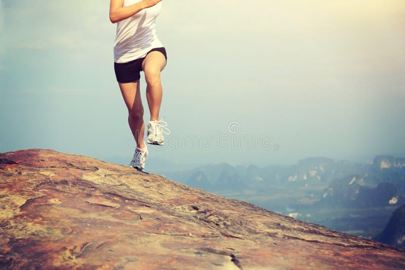 Caminhante asiático novo da mulher que corre no pico de montanha fotos de stock royalty free