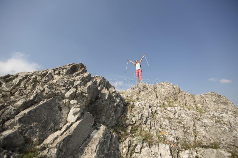Caminhante bem sucedido da mulher no pico de montanha imagens de stock