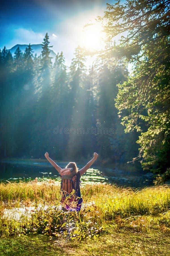 Caminhante Cheering da mulher com os braços abertos da trouxa no lago da montanha foto de stock royalty free