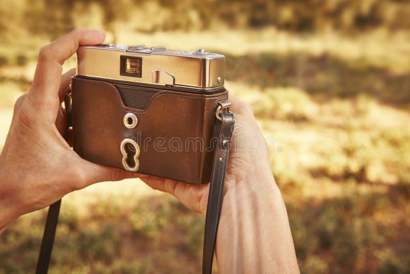 Caminhante com a câmera do vintage no campo Fundo do curso foto de stock royalty free