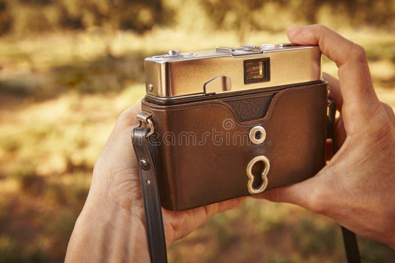 Caminhante com a câmera do vintage no campo Fundo do curso fotografia de stock royalty free