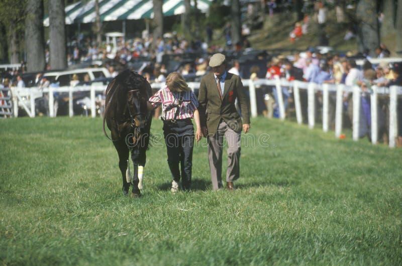 Caminhante com o cavalo durante a raça da corrida de obstáculos da mola, parque de Glenwood, Middleburg, Virgínia imagem de stock